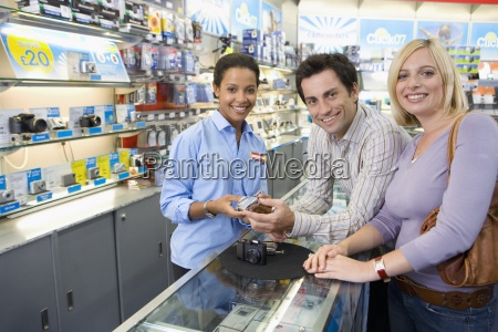 young couple with saleswoman looking at