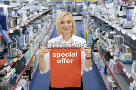 young woman in electronics aisle holding