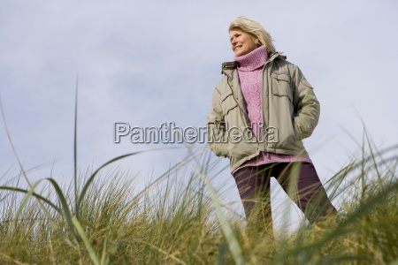 senior woman on sand dune smiling
