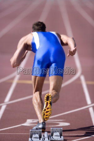 male athlete by starting blocks rear