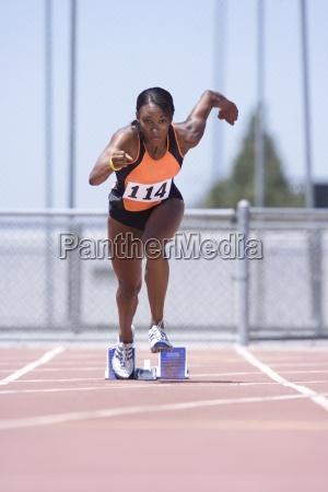 african female runner leaving starting block