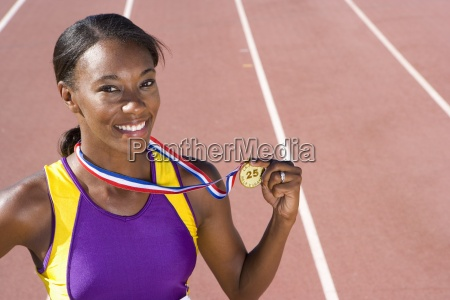 african female athlete displaying gold medal