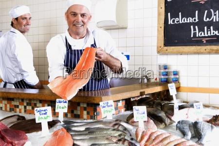 fishmonger detras de contador sosteniendo el