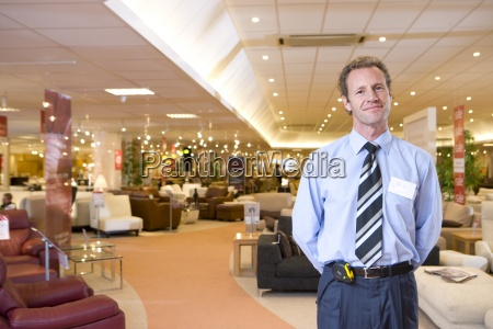 salesman in furniture shop smiling portrait