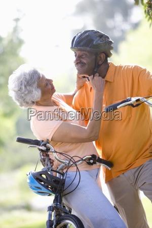 senior woman adjusting mans bicycle helmet
