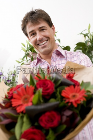 man with bouquet of flowers smiling