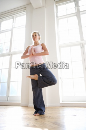 woman in tree pose low angle