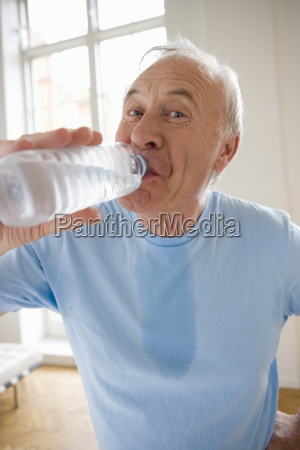 senior man drinking from water bottle