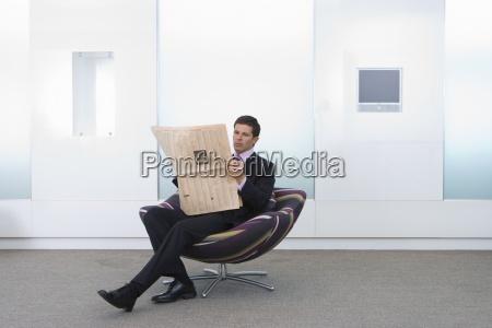 businessman reading newspaper in armchair