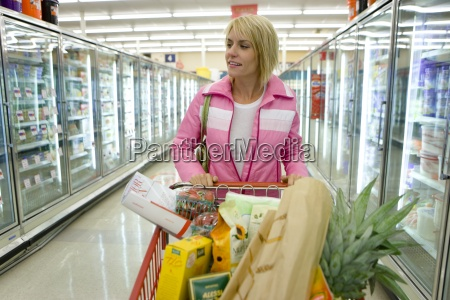 woman grocery shopping in frozen foods