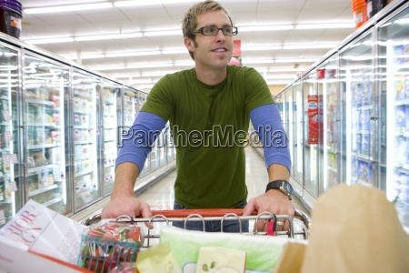 man grocery shopping in frozen foods