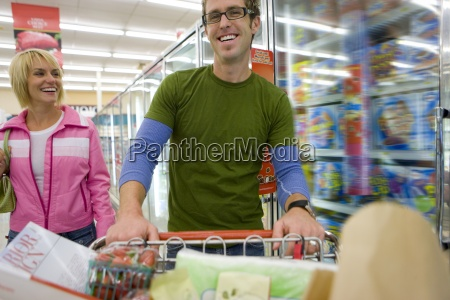 couple grocery shopping in frozen foods