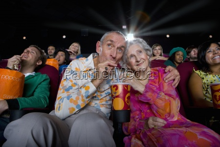 senior couple sharing drink in cinema