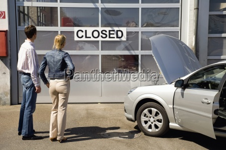 couple waiting at closed automotive garage