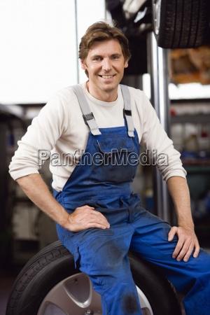 mechanic sitting on car wheel