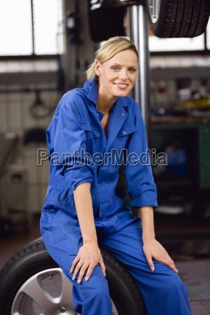 female mechanic sitting on car wheel