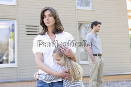 portrait of mother hugging daughter while
