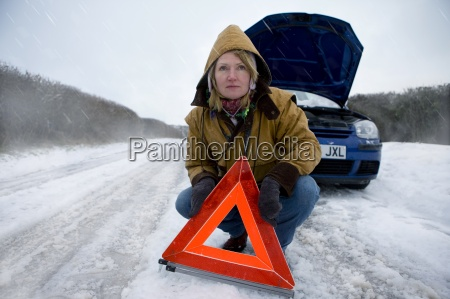 stranded woman placing caution sign near