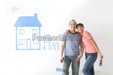 couple smiling next to house and