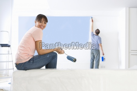 woman holding paint roller and smiling