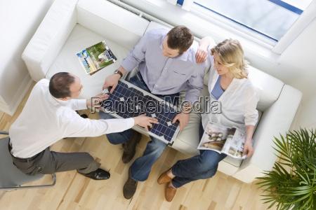 salesman showing solar panel to couple