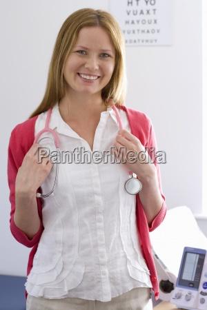 nurse with stethoscope smiling in examination