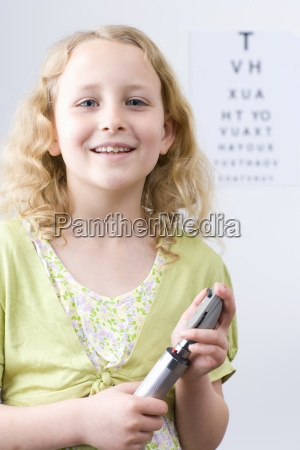 girl holding ophthalmoscope with eye chart