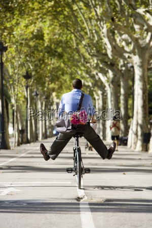 man cycling on treelined path with