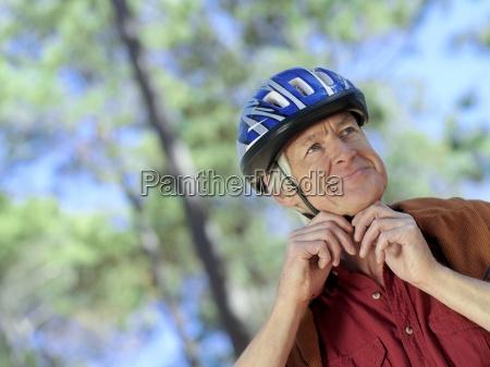active senior man adjusting strap on