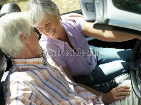 senior couple sitting in convertible face