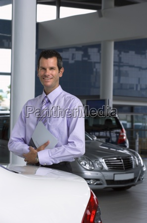 car salesman standing beside new car