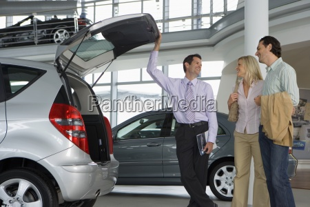car salesman showing couple new silver