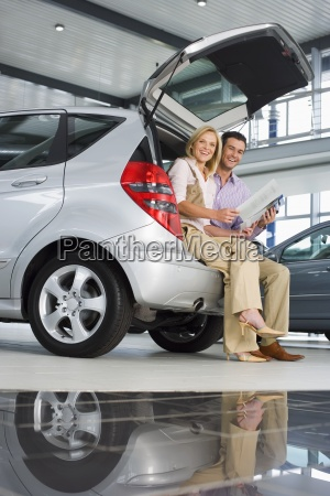 couple looking at new silver hatchback