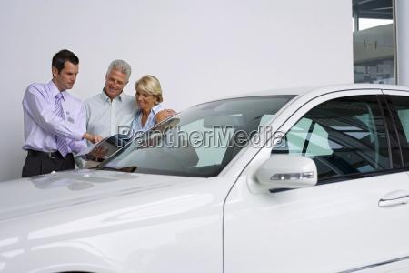 car salesman showing senior couple new