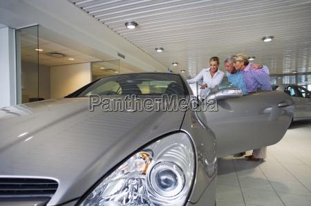 car saleswoman showing senior couple new