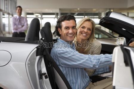 car salesman standing in large car