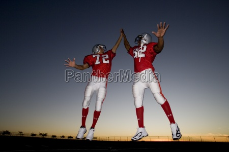 two american football players celebrating on