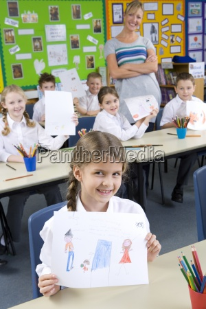 proud school children showing off drawings
