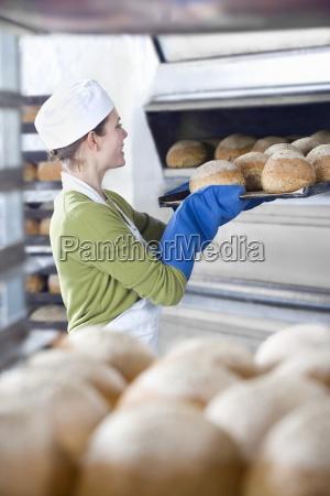 baker removing fresh loaves of bread