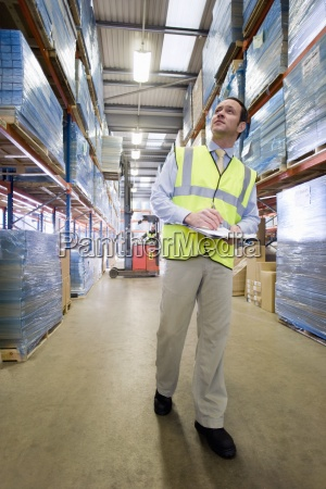warehouse manager holding clipboard and checking