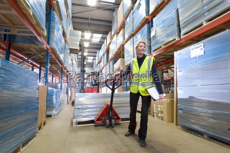 female warehouse manager holding clipboard and