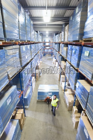 warehouse worker pulling pallet truck with