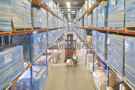warehouse worker inspecting box on forklift