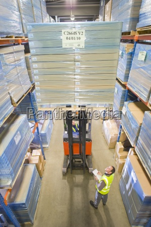 manager watching warehouse worker moving boxes