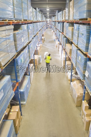 warehouse worker carrying boxes in aisle