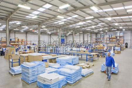 warehouse worker pulling pallet truck in