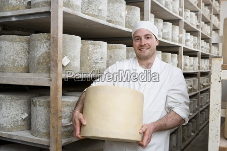 portrait of smiling cheese maker holding