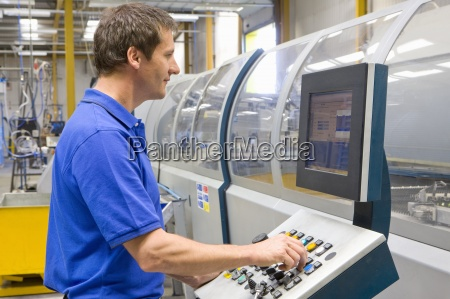 worker adjusting buttons on factory control