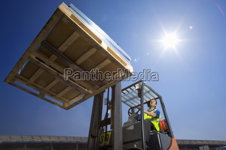 worker moving merchandise on forklift