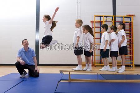 gym teacher watching school girl jump